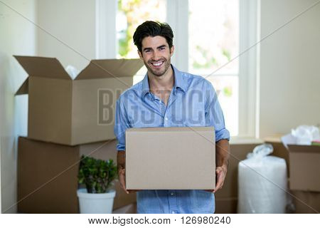 Portrait of young man standing with unpacking carton boxes in house