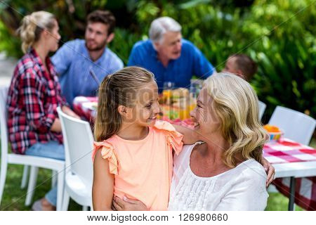 Granny carrying granddaughter against family having breakfast at yard