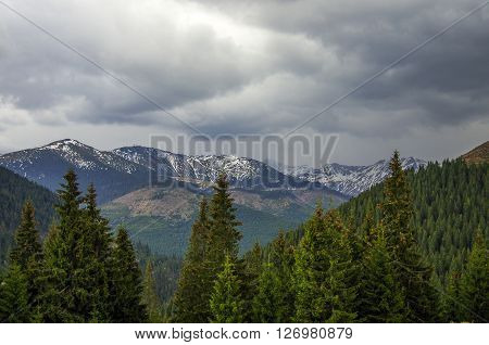 Panorama Of Carpathians Mountains With Stormy Clouds Sky And Snow On The Tops,transylvanian,romania,