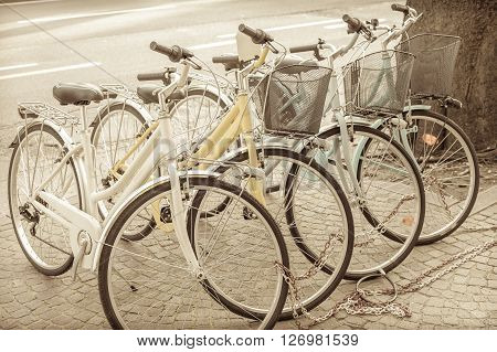 Four parked bicycles on the sidewalk chained together. Vintage effect.
