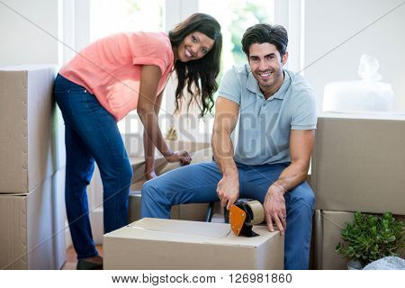 Portrait of young couple assisting each other while unpacking carton boxes in new house