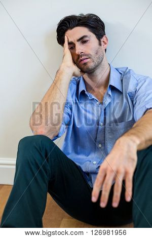 Depressed man with hand on forehead leaning against a wall at home