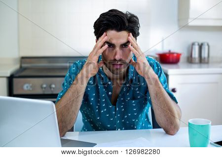 Tensed man sitting with bills and laptop in kitchen at home