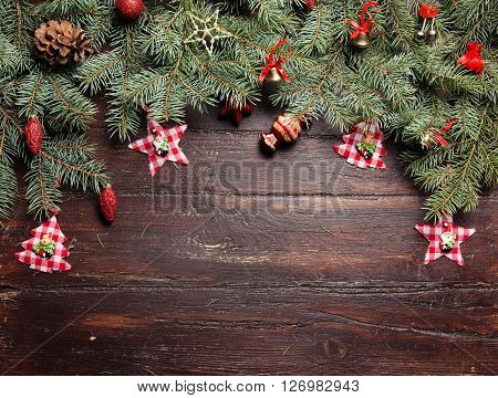 Christmas or New Year decoration background: fur-tree branches, colorful glass balls, decoration and glittering stars on wooden background, top view, copy space