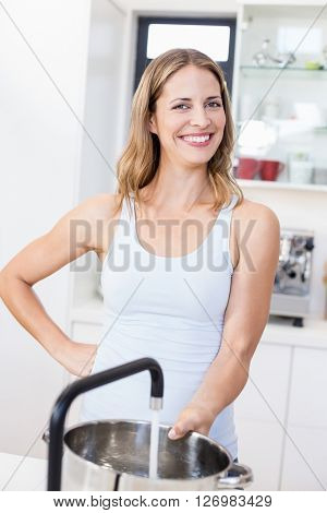 Happy woman holding a vessel under running tap in kitchen