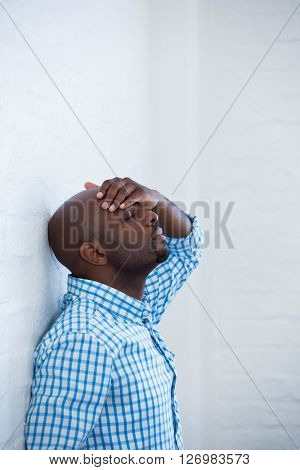 Upset man with eyes closed and hand on the forehead leaning against a wall in office