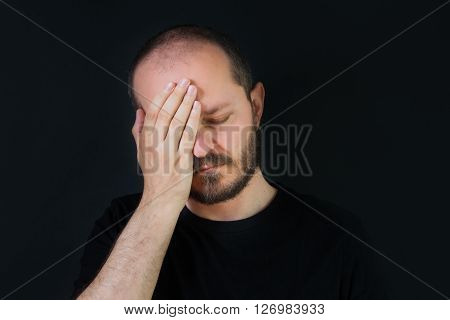 Serious man with beard and mustaches on black background, covering face with hand palm, face palm gesture