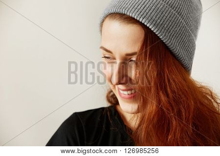 Isolated Headshot Of Cute Caucasian Redhead Freckled Girl In Black T-shirt And Gray Cap Smiling And