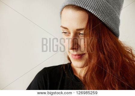 Headshot of attractive young female looking away with dreamy and mysterious smile. Close up studio portrait of pretty girl with loose red hair in cap and black T-shirt. Film effect selective focus