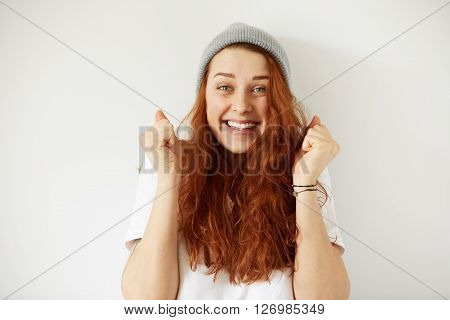Headshot Of Young Happy Female Wearing Gray Cap And T-shirt With Joyful Winning Smile. Close Up Isol