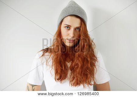 Close Up Studio Portrait Of Cute Young Female Looking At The Camera With Shy And Serious Expression.