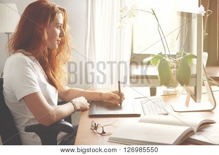 Portrait Of Young Female Freelancer Working At Home Using Digital Tablet. Redhead Woman Designer In