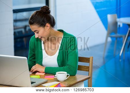 Woman looking at sticky notes with laptop on table in office