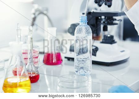 Close Up View Of Female Medical Researcher Or Doctor Using Glass Pipe And Plastic Bottle While Worki