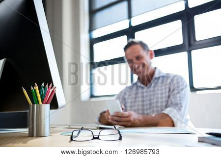 Spectacle and pen holder on desk in office and man using mobile phone in background