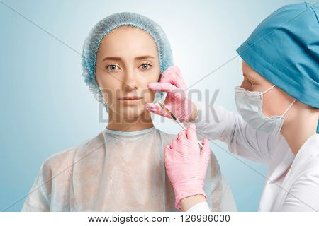 Close up isolated view of doctor in sterile gloves making facial injection in woman's cheek. Young Caucasian female having treatment cosmetic in beauty clinic. Aesthetic medicine cosmetology