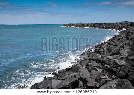 Volcanic stone's breakwater at atlantic ocean with blue sky