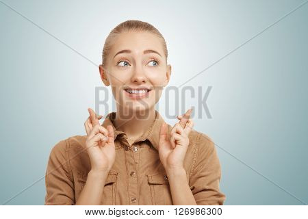 Close Up View Of Cheerful Young Blond Woman Crossing Her Fingers Against Blue Background. Isolated P