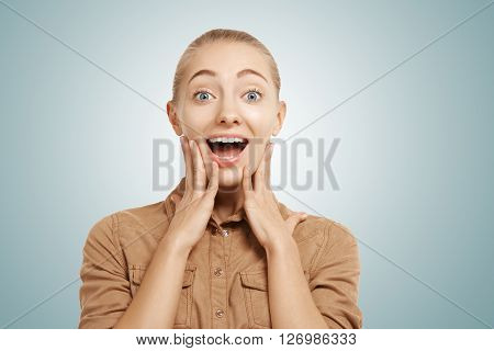 Close Up Isolated Portrait Of Attractive Surprised Young Girl Wearing Casual Beige Shirt Looking At