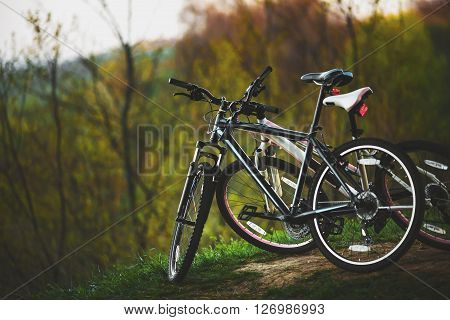 Biking. A romantic walk. Two bikes are at the top of the hill
