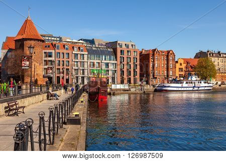 GDANSK, POLAND - APRIL 21, 2016: People at the quay port with many restaurants, pubs and Hilton Hotel in Gdansk. Old Town in Gdansk is a tourist attraction for visitors.