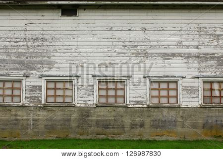 a picture of an exterior early 20th century barn wall with windows