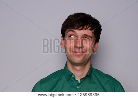leer European man in a green shirt on a neutral gray background. Dodgy emotion. Look up to the left with one eye half-closed