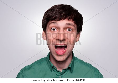 Caucasian man in fear emotion. portrait of a man with wide open mouth and eyes in green shirt