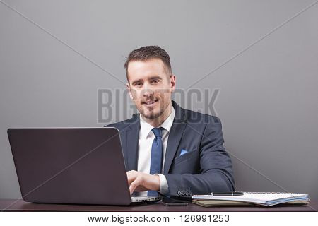 Handsome smiling business man working with laptop in office