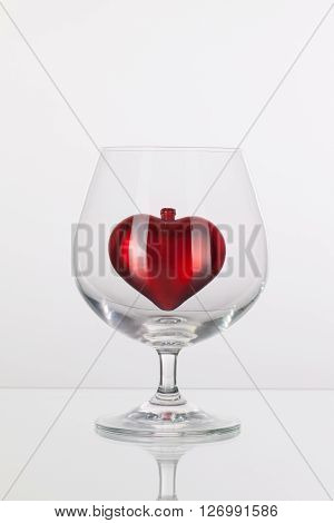 Red heart inside a glass of cognac on a glass plate