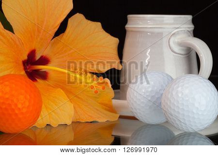 Orange hibiscus flowercup of coffee a golf balls on the glass plate