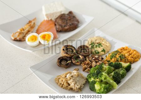 animal versus plant proteins: one plate with beef eggs salmon cheese and chicken grill and another with nuts mushrooms broccoli lentil hummus and quinoa