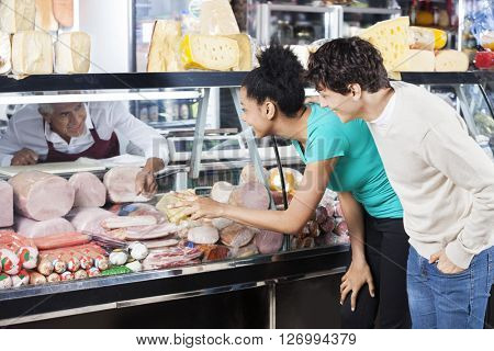 Couple Choosing Product From Display Cabinet While Salesman Assi