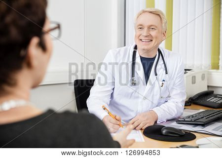 Male Doctor Looking At Female Patient At Desk