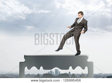Businessman walking carefully on old razor blade on city view background
