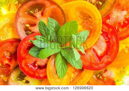 Close Up Of Colorful Tomato Slices With Green Twig Mint, Fresh Organic Food