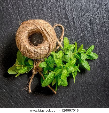Top Down Of Beautiful Bunch Fresh Green Mint Tied Rope And Yarn On Black Slate Background, Close Up