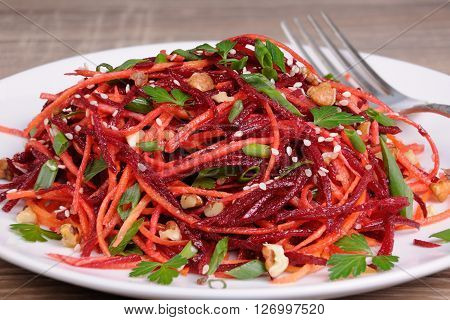 Salad of fresh grated carrots beets onions flavored with nuts and sesame seeds