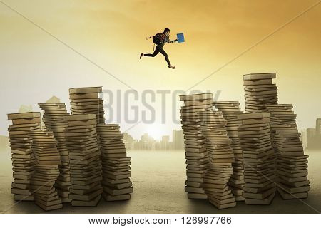 Picture of a female college student carrying bag and jumping over the pile of book