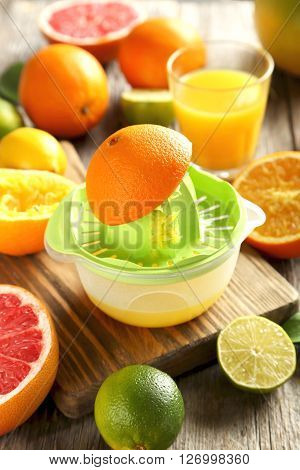 Citrus Fruits With Juicer On A Grey Wooden Table
