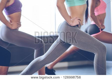 Feel burn in buttocks. Side view part of young women with perfect buttocks in sportswear exercising while standing in front of window at gym