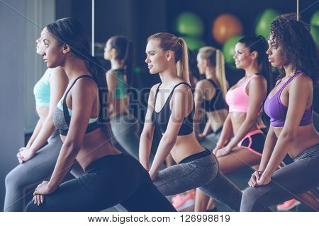 Feel how stretchy you are girls! Side view of beautiful young women with perfect bodies in sportswear exercising with smile at gym