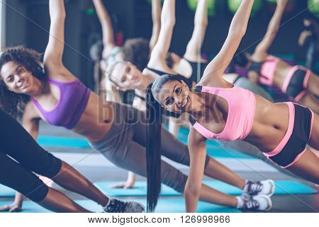 Side plank. Close-up part of young beautiful women with perfect bodies in sportswear doing side plank and looking at camera with smile at gym