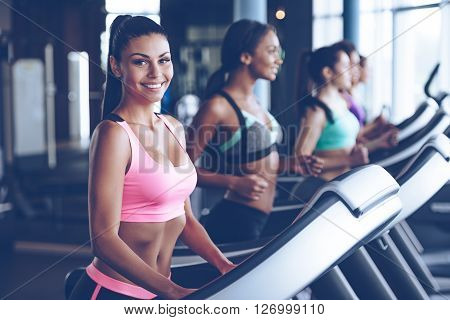 Sporty beauty. Beautiful young cheerful woman in sportswear looking at camera with smile while running on treadmill at gym with other women