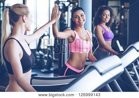 We did it! Side view of young beautiful women looking at each other and giving high-five with smile while running on treadmill at gym