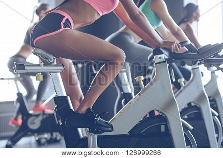 Power and motivation. Side view part of young women with perfect bodies in sportswear looking at camera with smile while cycling at gym