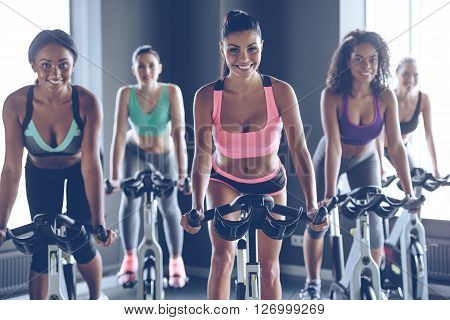 Cycling beauties. Young beautiful women with perfect bodies in sportswear looking at camera with smile while cycling at gym