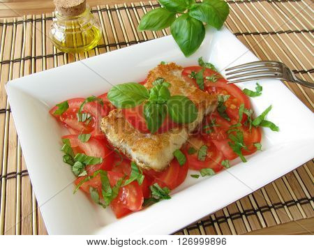 Homemade fish filet with tomatoes and basil