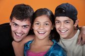 foto of reunited  - Two caring brothers with sister smiling on orange background - JPG