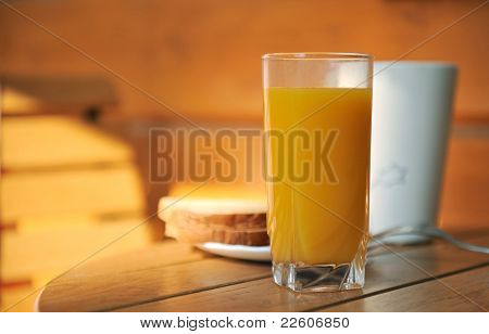 Glass of juice and toasts on a table in a garden